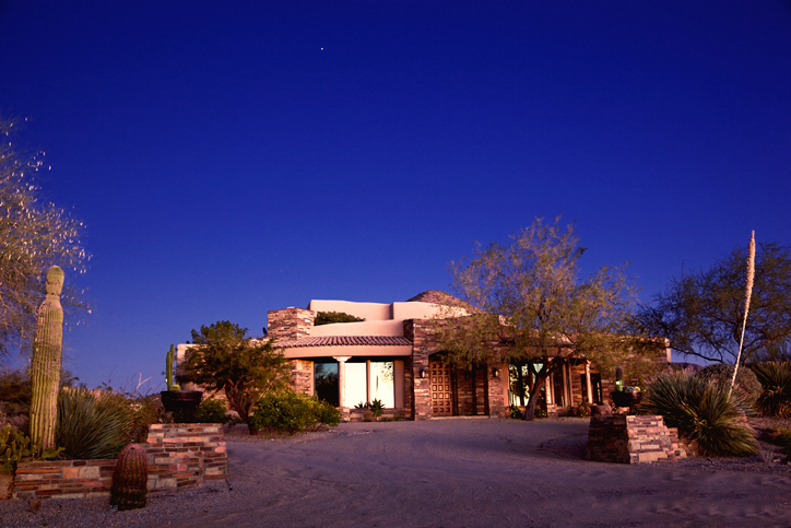 Luxury North Phoenix and Scottsdale, AZ modern stone and adobe home  in a desert landscape setting on a clear sky at twilight, clear blue night sky